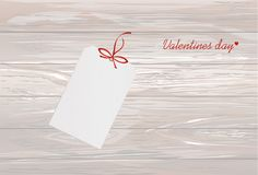 Gift card tied with a red heart. Vector. Valentine`s Day. On woo. Den background Greeting card for the holiday Royalty Free Stock Image