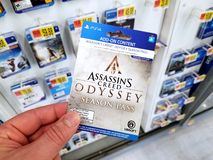 Gift card of a video game in a hand. PLATTSBURGH, USA - JANUARY 21, 2019 : Add on card of Assassins Creed Odyssey video game in a hand of a buyer at Walmart royalty free stock photos