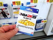 Gift card of a video game in a hand. PLATTSBURGH, USA - JANUARY 21, 2019 : Add on card of 2k19 NBA video game in a hand of a buyer at Walmart store, cards, shop royalty free stock photography