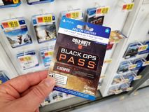 Gift card of a video game in a hand. PLATTSBURGH, USA - JANUARY 21, 2019 : Call of Duty Black Ops video game Pass card for PS4 in a hand of a buyer at Walmart royalty free stock photo