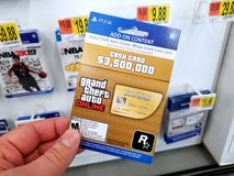 Gift card of a video game in a hand. PLATTSBURGH, USA - JANUARY 21, 2019 : Cash card of Grand Theft Auto video game in a hand of a buyer at Walmart store, gift stock photo