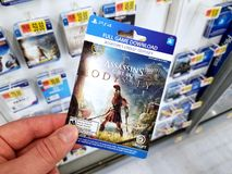 Gift card of a video game in a hand. PLATTSBURGH, USA - JANUARY 21, 2019 : Full game download card of Assassins Creed Odyssey video game in a hand of a buyer at stock image