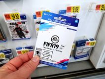 Gift card of a video game in a hand. PLATTSBURGH, USA - JANUARY 21, 2019 : Full download card of Fifa 19 video game in a hand of a buyer at Walmart store, soccer royalty free stock photos