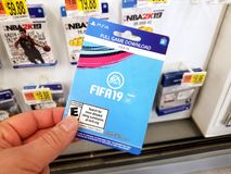 Gift card of a video game in a hand. PLATTSBURGH, USA - JANUARY 21, 2019 : Full download card of Fifa 19 video game in a hand of a buyer at Walmart store, soccer royalty free stock images