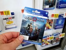 Gift card of a video game in a hand. PLATTSBURGH, USA - JANUARY 21, 2019 : Full game download card of God of War video game in a hand of a buyer at Walmart store royalty free stock photo