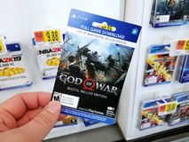 Gift card of a video game in a hand. PLATTSBURGH, USA - JANUARY 21, 2019 : Full game download card of God of War video game in a hand of a buyer at Walmart store stock photography