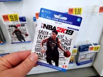 Gift card of a video game in a hand. PLATTSBURGH, USA - JANUARY 21, 2019 : Full game download card of 2k19 NBA video game in a hand of a buyer at Walmart store stock image