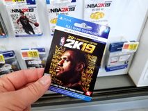 Gift card of a video game in a hand. PLATTSBURGH, USA - JANUARY 21, 2019 : Full game download card of 2k19 NBA video game in a hand of a buyer at Walmart store stock images