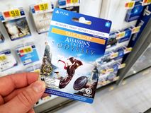 Gift card of a video game in a hand. PLATTSBURGH, USA - JANUARY 21, 2019 : Season Pass card of Assassins Creed Odyssey video game in a hand of a buyer at Walmart stock images
