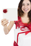Gift card woman with a gift box. Smiling friendly woman showing a gift card with copy space and holding a gift box Royalty Free Stock Images
