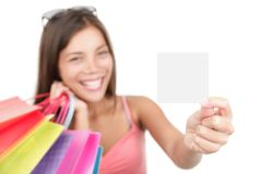 Gift card woman shopping. Shopping woman showing sign or blank card. Chinese Asian / Caucasian isolated on seamless white background. Focus on the blank sign / Stock Photo