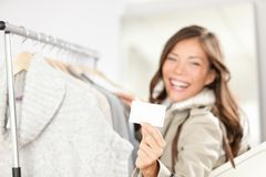 Gift card woman shopping clothes. Happy shopper holding showing gift card or business card in store while shopping for clothing Royalty Free Stock Photos