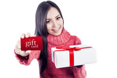 Gift card for you isolated in white. Asian woman is showing a gift card while holding a present Stock Photography