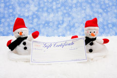 Gift Certificate. A blank gift certificate with a snowman sitting on snow background, gift certificate stock photo