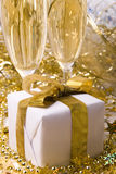Gift and champagne. Two glasses of champagne and gift with golden bow Stock Image