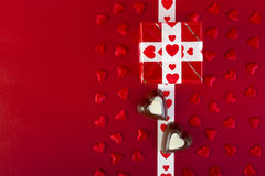 Gift and chocolate and red hearts on red Stock Image