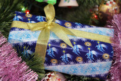 Gift on chrismas tree Stock Images