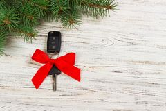 Gift for christmas car keys. Close-up view of car keys with red bow as present on wooden background.  Royalty Free Stock Images