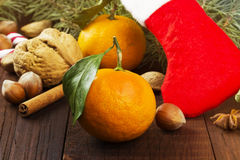 Gift in Christmas sock - tangerine, candy, nuts, cinnamon  Royalty Free Stock Photos