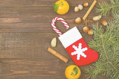 Gift in Christmas sock - tangerine, candy, nuts, cinnamon  Stock Photo