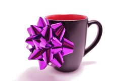 Gift of Coffee. Black coffe cup with red inside and a shiny purple bow on the side Stock Photo