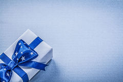 Gift container with tied bow on blue background holidays concept Royalty Free Stock Photos