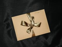 Gift craft envelope with golden ribbon and sign `for you` on black background. Valentine`s Day Gift. Craft paper envelope with a handwrite sign `for you` and stock photos