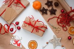 A gift in craft paper tied with a red ribbon surrounded by Christmas trivia, balls, garlands, dried oranges, wooden toys stock photos