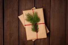 Gift in craft paper and tied with twine and fir decorated on a rustic dark wooden table. Space for text. Christmas royalty free stock image