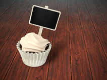 Gift cupcake with blank chalkboard signboard label on dark wood Stock Image