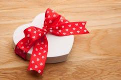 Gift in de vorm van hart met rood lint met een boog wordt gebonden die Royalty-vrije Stock Foto