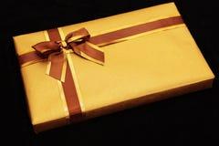 Gift die in goud met bruin/gouden lint wordt verpakt Royalty-vrije Stock Foto