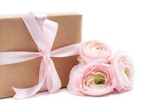 Gift die met lint en roze bloemen wordt gebonden stock fotografie