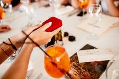 Gift in een hand van meisje dichtbij cocktail stock fotografie