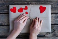 Gift in een kraftpapier-document met rode harten wordt verpakt dat Royalty-vrije Stock Afbeeldingen