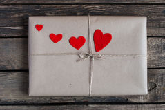 Gift in een kraftpapier-document met rode harten wordt verpakt dat Stock Foto