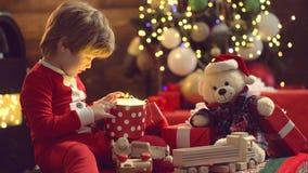 Gift emotions. Kid having fun near Christmas tree indoors. Funny kid holding Christmas gift. Cute little kids