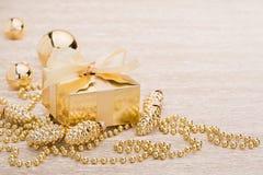 Gift en gouden Kerstmisbal op verlichte achtergrond royalty-vrije stock afbeeldingen