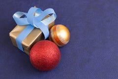 Gift en Kerstmisballen op purpere achtergrond Royalty-vrije Stock Fotografie