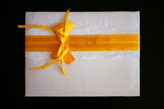 Gift envelope with a yellow ribbon. White gift envelope with a yellow ribbon royalty free stock image
