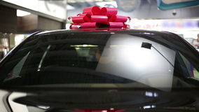 Gift expensive black car with red symbolic ribbon on a roof.  stock video footage