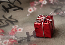 Gift on the fabric with hieroglyphics. Gift on the fabric with sakura flowers and hieroglyphics Stock Images