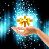 Gift in a female hand on a winter background Royalty Free Stock Photos
