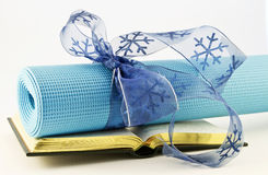 Gift of Fitness Lies in Study of Yoga. Serene blue yoga mat wrapped with blue ribbon placed with open book; fitness, study, and yoga are gifts of healthy Royalty Free Stock Images