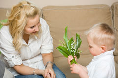 Gift flowers for my mom. Gift flowers for my mom, baby son and his mother habving fun Royalty Free Stock Photo