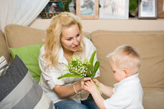 Gift flowers for my mom. Gift flowers for my mom, baby son and his mother habving fun Stock Image