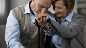 Gift folk för pensionär som tillsammans sitter hållande händer på den gå pinnen, closeness arkivbild