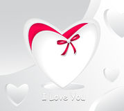Gift in form white heart and with red bow pearl. White abstract background Royalty Free Stock Photos