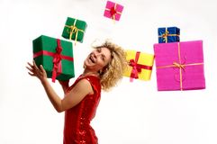 Gift Frenzy. A young Caucasian woman with curly blond hair holds a present in her hands while numerous other colorfully-wrapped presents are suspended in the air Royalty Free Stock Photography