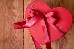 Gift of giftdoos met een rode boog van een lint in de vorm van een hart op een rustieke achtergrond voor Valentijnskaartendag stock fotografie